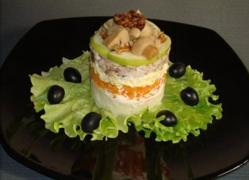 Portion layered salad with chicken, apple, nuts and mushrooms