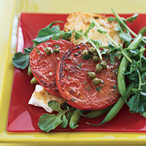 Grilled tomatoes on a baking sheet and salad with feta cheese with lemon caper sauce