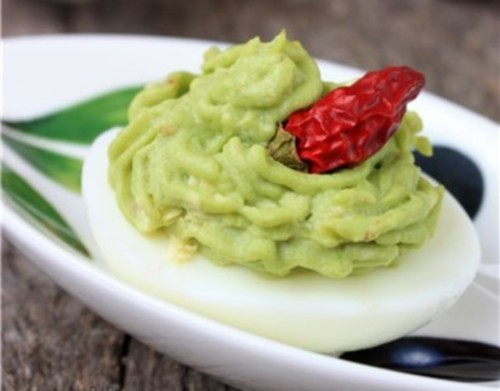 Appetizer of stuffed eggs with guacamole