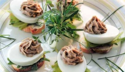 Appetizer of eggs stuffed with tuna in pistachios